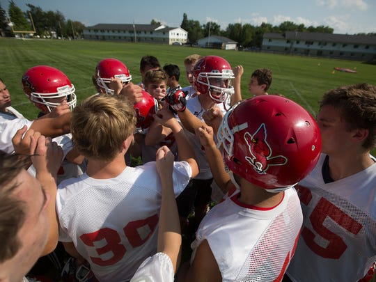 The Pacelli football team huddles up during football practice at Pacelli High School, Tuesday, Aug. 2, 2016.