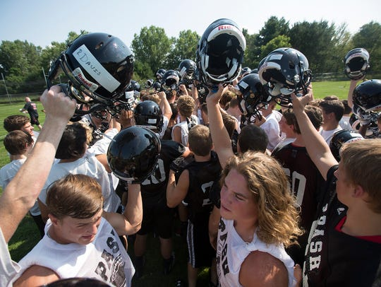 The SPASH football team huddles up during football