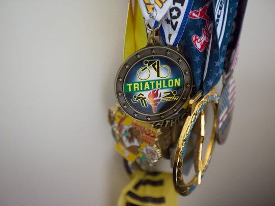 Kathy Hermann's medals from competing in triathlons hang on display at her apartment in Stevens Point, Saturday, July 2, 2016.