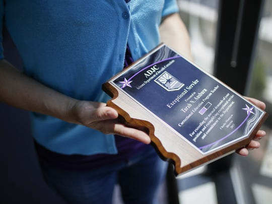 Tarah Ausburn holds a service award she received from
