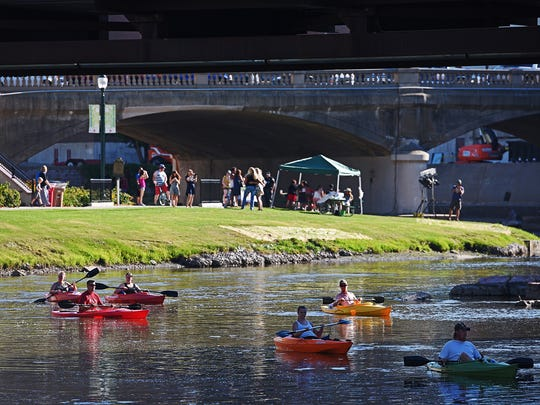 A group of kayakers paddle by during Downtown Riverfest