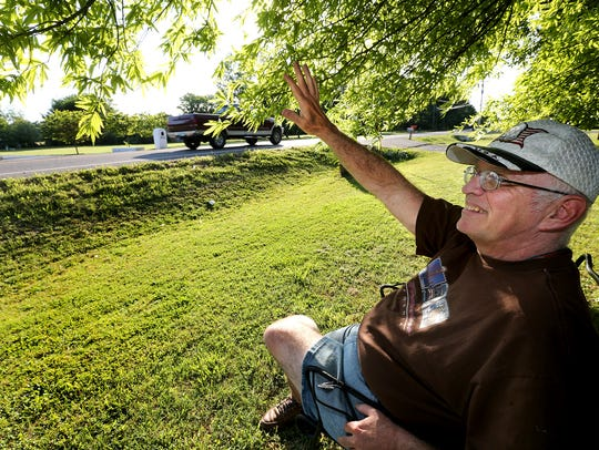 Paul Tidwell sits on his front lawn and waves at passers-by