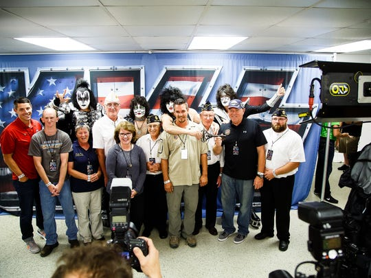 "Iowa veteran Dustin Patrick, 38 from Altoona, center, who is receiving a home from the Military Warriors Support Foundation meets the band Kiss before they perform at the Iowa State Fair on Friday, August 19, 2016, in Des Moines. ""It doesn't feel real,"" said Patrick."