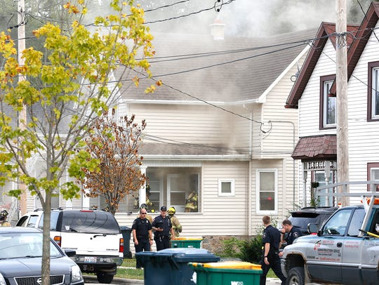 Police and fire officials work the scene of a house