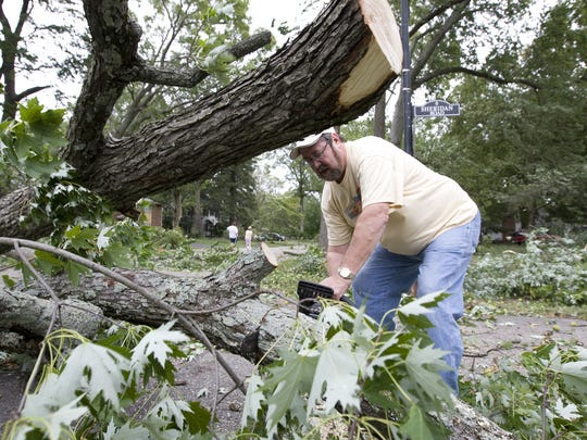 Glenn Martin cleared trees from the road in Avondale in Hikes Point. Sept. 14, 2008. The massive wind storm took a large toll on Louisville area trees.