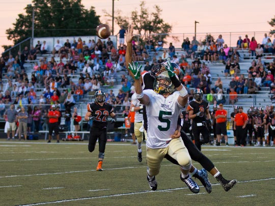 A pass intended for York Catholic tight end Ryan Sewell (5) gets broken up by York Suburban's Isaiah House during the second quarter Friday.