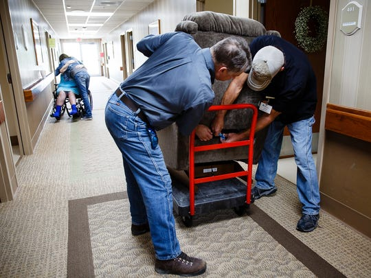 Northern Mahaska Specialty Care maintenance man John Isley, 48 of Oskaloosa, right, and Carl Haffner put together Diane Davis' new motorized as she gets a hug in the background at the nursing home in Oskaloosa on Friday, September 2, 2016.