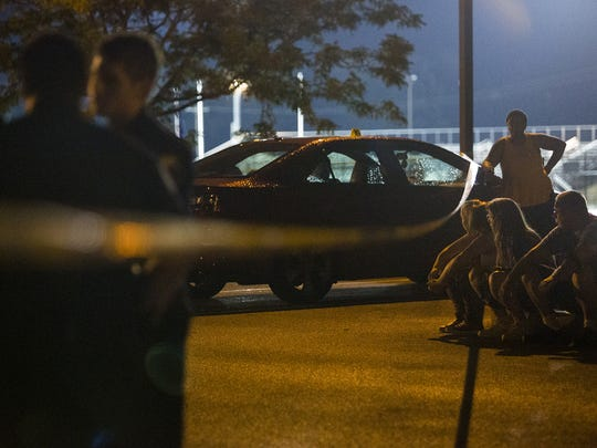 People wait for their cars to be released from the scene after Friday night's shootings. Two people were shot near Small Athletic Field during a high school football game. The shooting took place during the William Penn home football game against J.P. McCaskey. The game was called, with the final score 26-6 McCaskey.