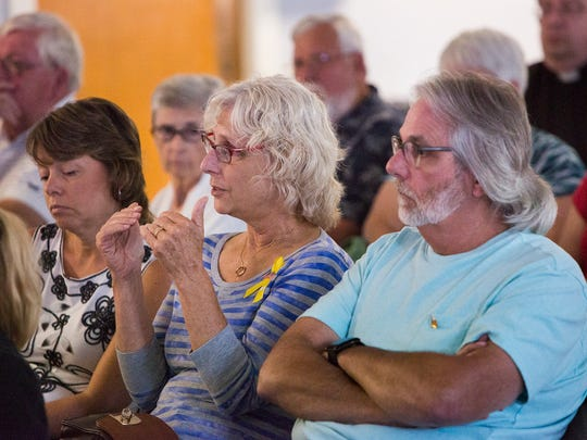 Nancy Taylor, 65, of Shiloh, center, asks Salaam Bhatti a question after Bhatti's presentation.