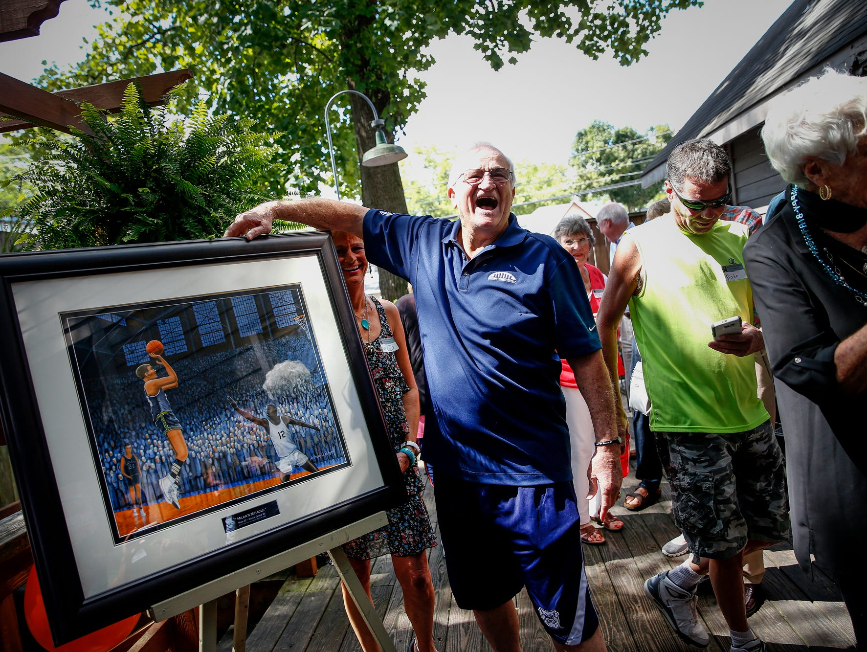 Bobby Plump shows his excitement after a commissioned painting by Anthony Padgett was unveiled during Plump's 80th birthday party on Sept. 11, 2016.