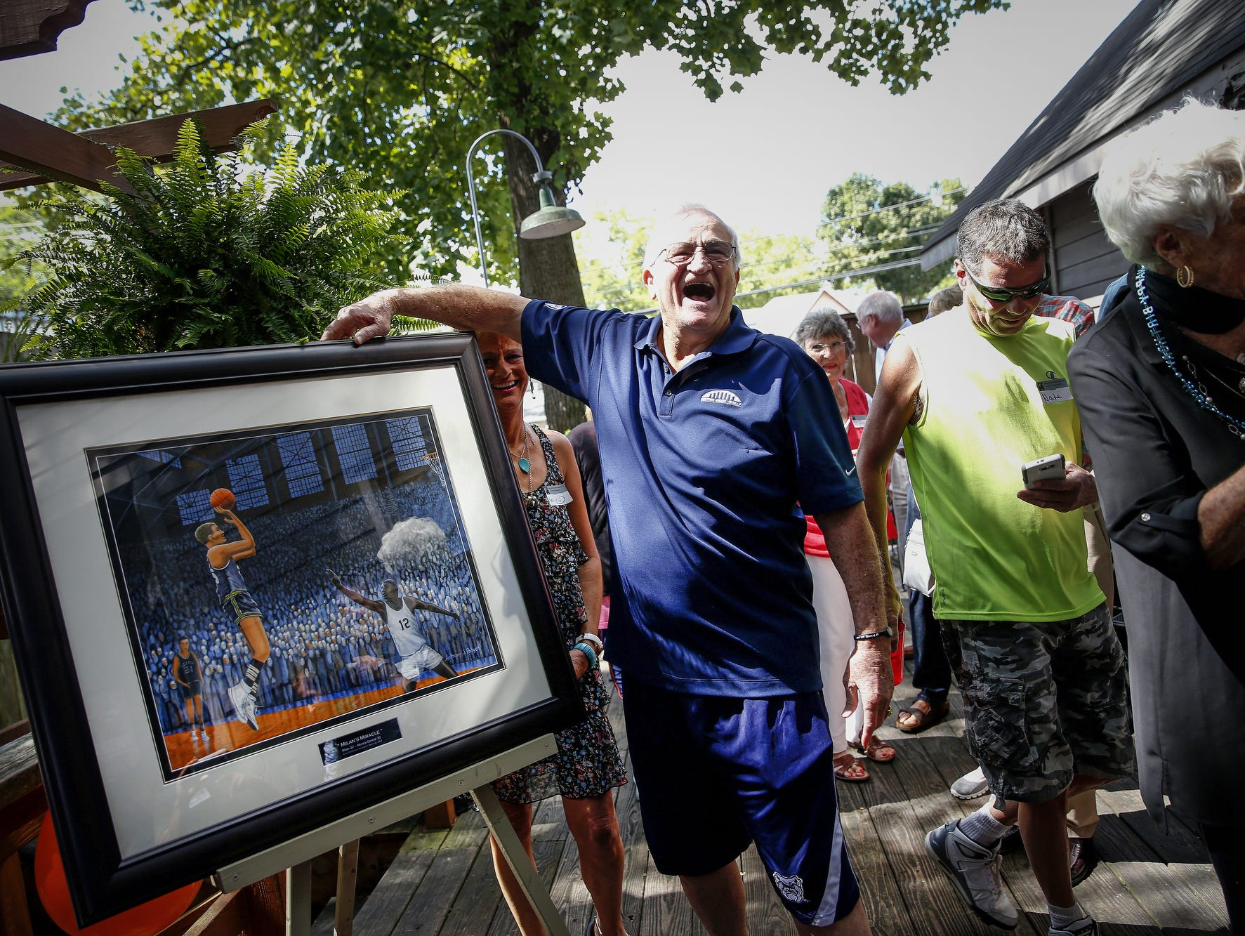 Bobby Plump shows his excitement after a commissioned painting by Anthony Padgett was unveiled during Plump's 80th birthday party Sunday.