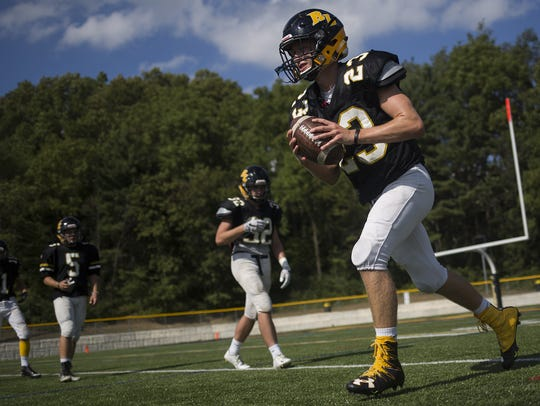 Red Lion quarterback Sam Emig, right, works on a drill