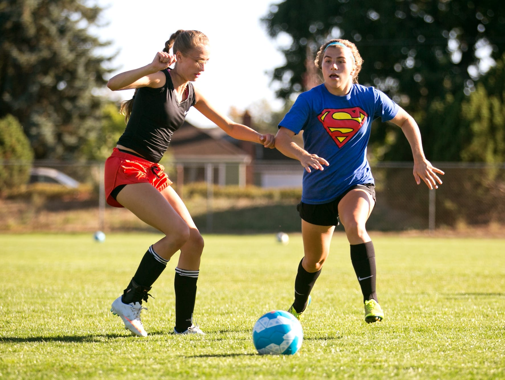 Defensive center midfielder Emily Collier (right) dribbles past Trinity Phillips at a practice for Blanchet Catholic School on Monday, Sept. 12, 2016.