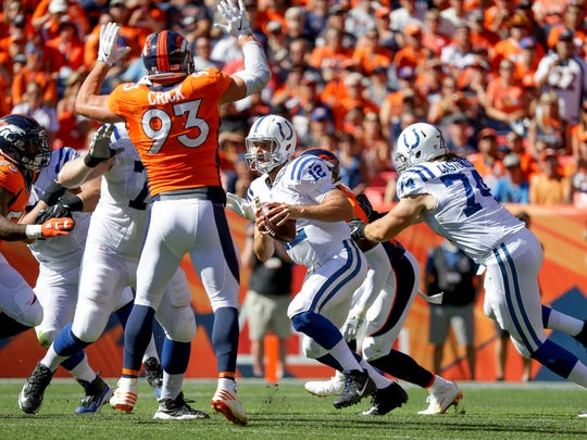 Indianapolis Colts quarterback Andrew Luck (12) is pressured by the Denver Broncos defense during the second quarter at Sports Authority Field at Mile High in Denver on Sunday, September 18, 2016.