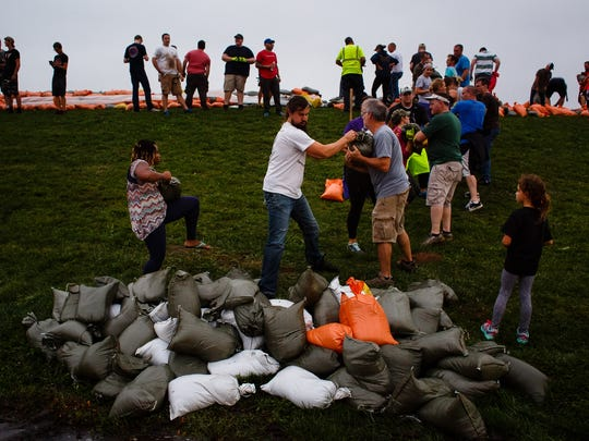 People help to sandbag as water levels in the Cedar River are expected keep rising overnight on Friday, Sept. 23, 2016, in Cedar Falls.