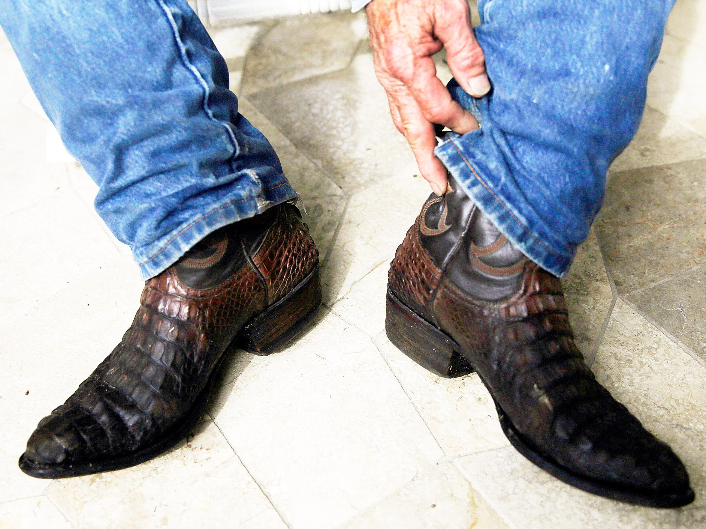 Kelvin Townsend wears his custom alligator skin boots in his home on Monday, Aug. 29, 2016. Townsend owns Townsend and Sons Gator Farm and Processing which does the processing for All American Gator Products, which is owned by Brian Wood.