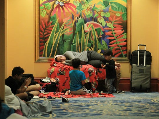 Guests rest in a hallway at the Atlantis Paradise Island hotel, as they stay far away from their rooms' windows during the passage of Hurricane Matthew in Nassau, Bahamas, Thursday, Oct. 6, 2016.