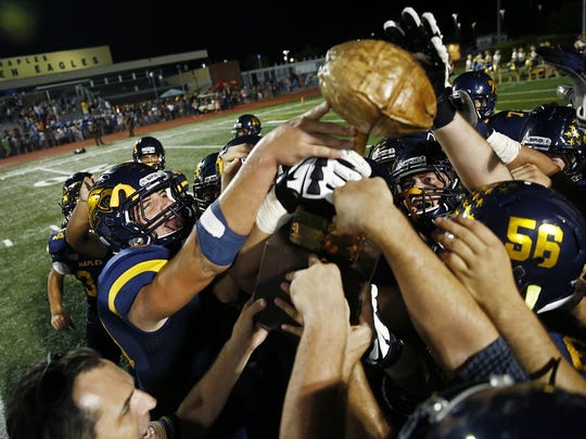 """The Naples High School football team celebrates with the Joe Klimas Trophy or colloquially called """"The Nut,"""" after defeating Lely on Friday, Oct. 9, 2015 at Naples High School's Staver Field in Naples, Fla. The Golden Eagles faced The Trojans in the 42nd annual Coconut Bowl. Naples won 69-0."""