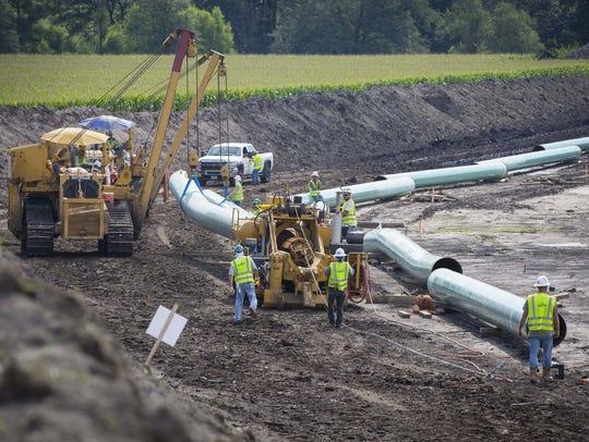 A  crew positions pipe segments near Baxter, Iowa,