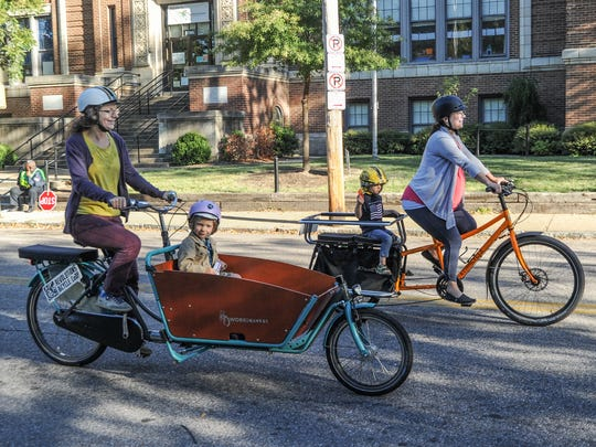 "Sylvia Crum (left) rides her son, Charlie, in a utility bike from the Netherlands called a WorkCycles ""Bakfiet"" which simply means ""bike with a bucket."" Her friend, Ellen Cumba, rides her son, Alijah, on a utility bike called an Xtracycle ""Edgerunner,"" with a passenger cart complete with saddle bags for carrying items."