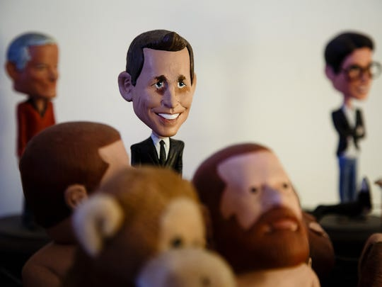 Completed bobbleheads sit on a shelf as Bryan Guise