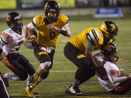 Red Lion quarterback Sam Emig, center, has rushed for a league-high 14 touchdowns this season, a testament to the work done by a seasoned offensive line.