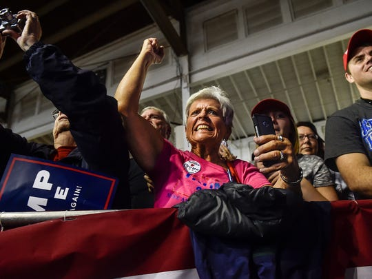 Fans of Donald Trump cheer as he takes the stage at