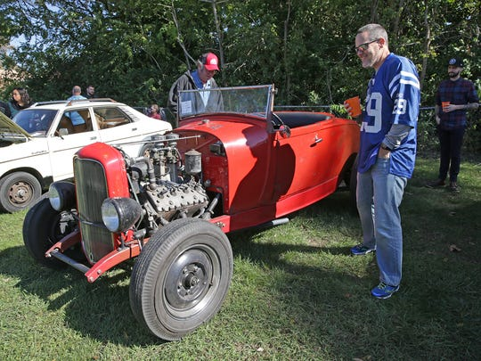 David Johansen, left, and Dave Bradley, right, look over a 1929 Ford hot rod, at the Broad Ripple Brewpub Hoods & Hops Classic Car Show, held at Opti-Park in Broad Ripple, Sunday October 23rd, 2016.