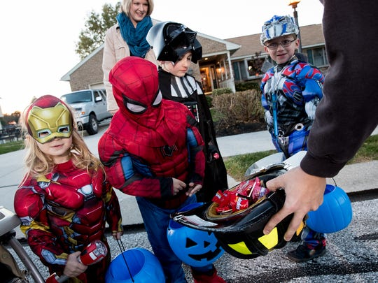 Trick or treaters wait for candy from Penn Township firefighter Shane Baker on Northview Drive in Hanover on Tuesday.