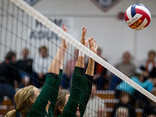 D.C. Everest front row, jumps up to block a spike from the Marshfield in a Division 1 sectional semifinal at SPASH on Thursday night.