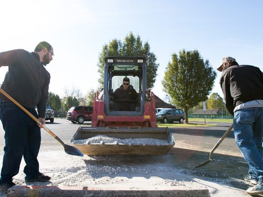 Zachary Dom, left, and Wade Harlaub, right, shovel up gravel as Brandon Merritts operates a skid loader in Littlestown Community Park on October 29, 2016. A group of several volunteers gathered in the park on Saturday to help Boy Scout Travis Hartlaub construct a Veterans Memorial for his Eagle Scout Service project.