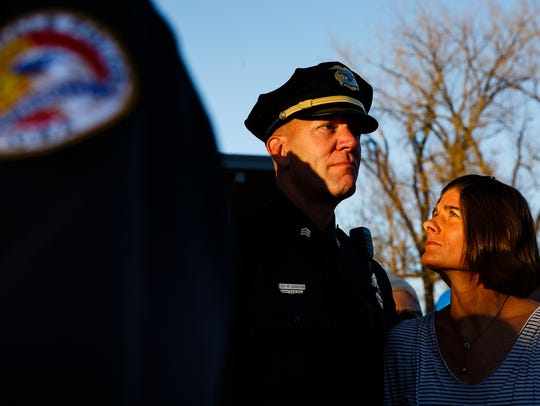 Julie Jorgensen, right, looks up at her husband Sgt. Mark Jorgensen before a candlelight vigil in honor of Officer Justin Martin and Sgt. Anthony Beminio on Friday, Nov. 4, 2016, in Urbandale.