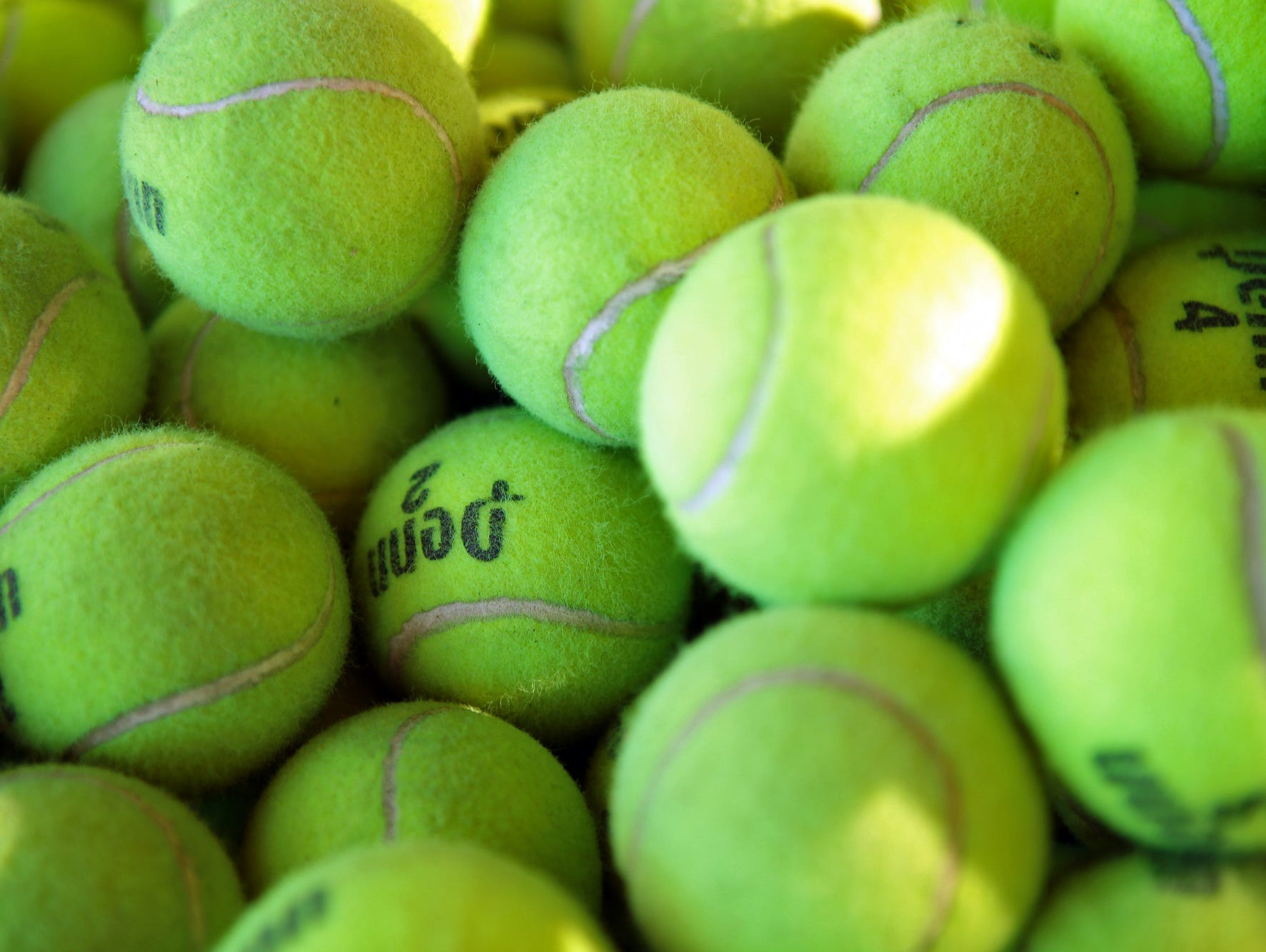 Practice tennis balls are in a bucket at Plaza Racquet Club in Palm Springs, Calif. on March 5, 2015.