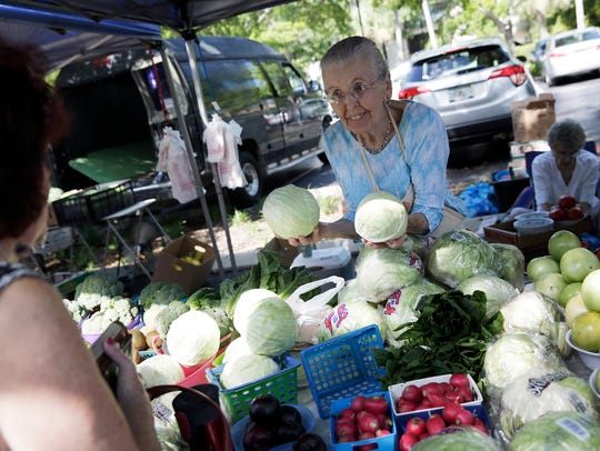 Yvonne Moore of Jan's Produce helps customers at the