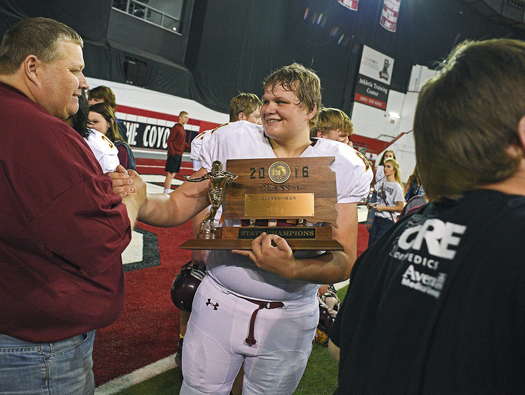 Madison's Luke Palmquist (69) holds their trophy while celebrating their 39-0 win over Tea Area with their fans and families after the 2016 South Dakota State Class 11A Football Championship game Saturday, Nov. 12, 2016, at the DakotaDome on the University of South Dakota campus in Vermillion, S.D.