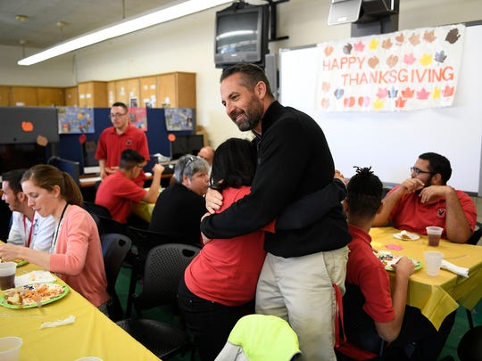 Special education teacher Jerry Mercadante hugs a student during the Thanksgiving Day meal the class prepared for classmates and staff of Manchester Regional High School's in Haledon, NJ on Tuesday, November 22, 2016.