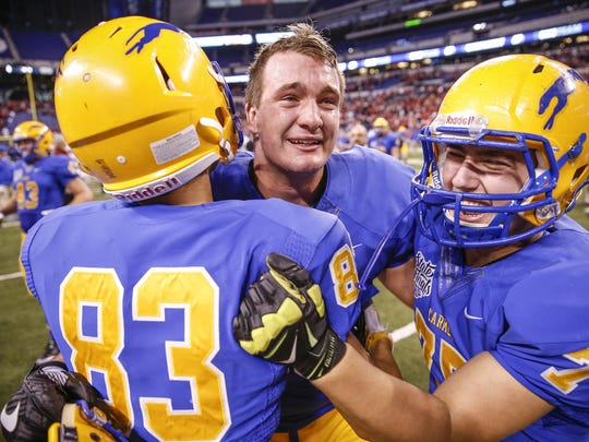 Carmel Greyhounds' Britt Beery (88) hugs teammates after their team's 16-13 win against Center Grove in the Class 6A state title game at Lucas Oil Stadium on Friday, Nov. 25, 2016.