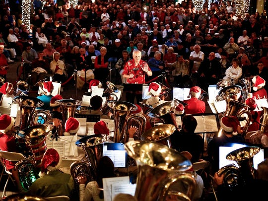 Michael Boudreau leads the musicians during the 19th annual Tuba Christmas performance in   2014, in the Sugden Plaza in downtown Naples.  They return this week.(Scott McIntyre/Staff)