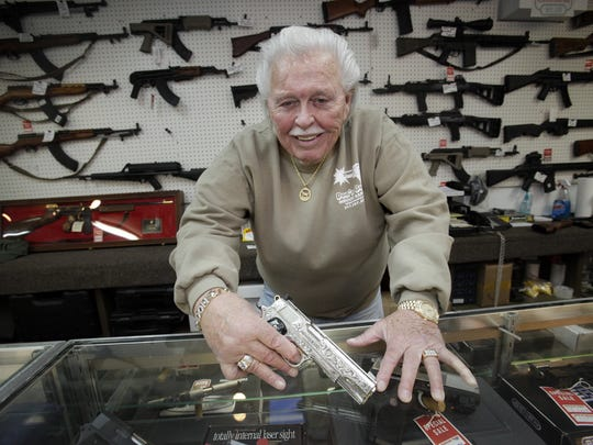 Don Davis holds a Colt 45 at his store, Don's Guns on Lafayette Road, Dec. 15, 2010.