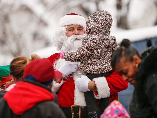Santa hands out toys and speaks with young kids during