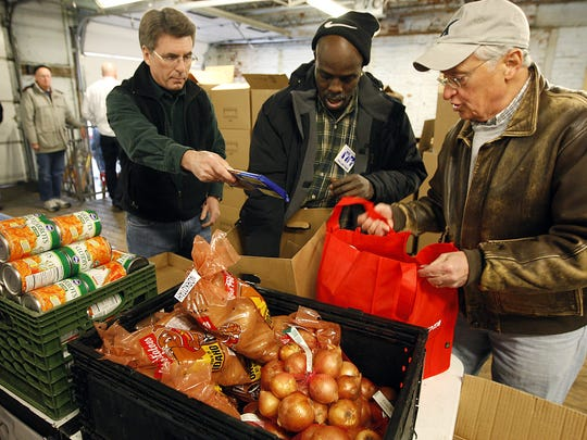 TUESDAY METRO DECEMBER 21, 2010. Volunteers Jim Dodd of Union Twp., left, Tod Dodds of West End and Jim McCafferty of Anderson pack food that was distributed for Christmas food baskets at St. Vincent de Paul Outreach. The three where part of the 60 volunteers who helped distribute the food. St. Vincent de Paul's provided over 600 Christmas food baskets full of a choice of turkey, ham, or chicken along with vegetables and other side items. St. Vincent de Paul expected a 25% more increase than last year. About 3,500 local families were helped with the food distribution and Christmas gifts through the Adopt-a-Family Program.  Photo shot Tuesday December 21, 2010. The Enquirer/Cara Owsley