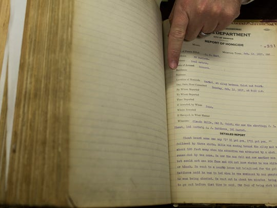 Memphis Police Sergeant Joe Stark points out Memphis' oldest unsolved murder from February 13, 1917, inside of a large book that documents all of the homicides in Memphis from 1917 through 1936.