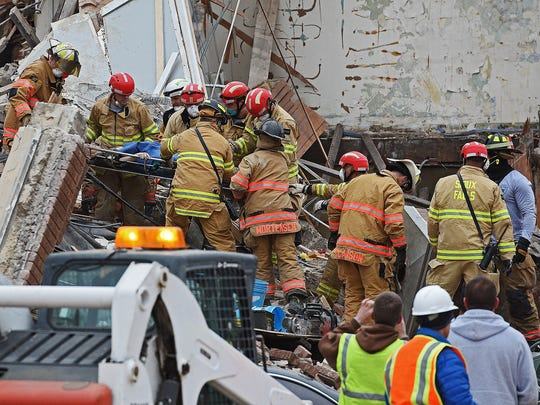 A woman is rescued from the rubble by emergency personnel
