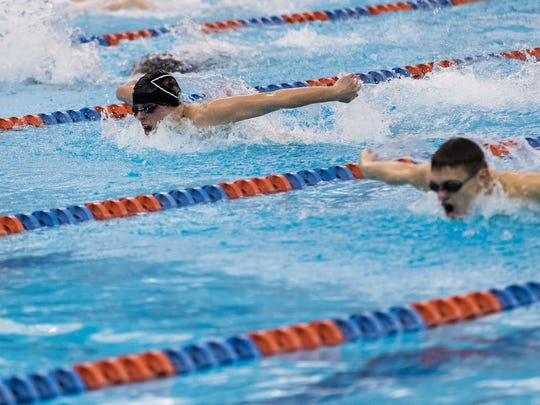 Gettysburg's Jared Herr (top) and York Suburban's Karl Schmittle swim the 100 butterfly at Gettysburg College on Jan. 9. The Trojans defeated the Warriors 93-77.
