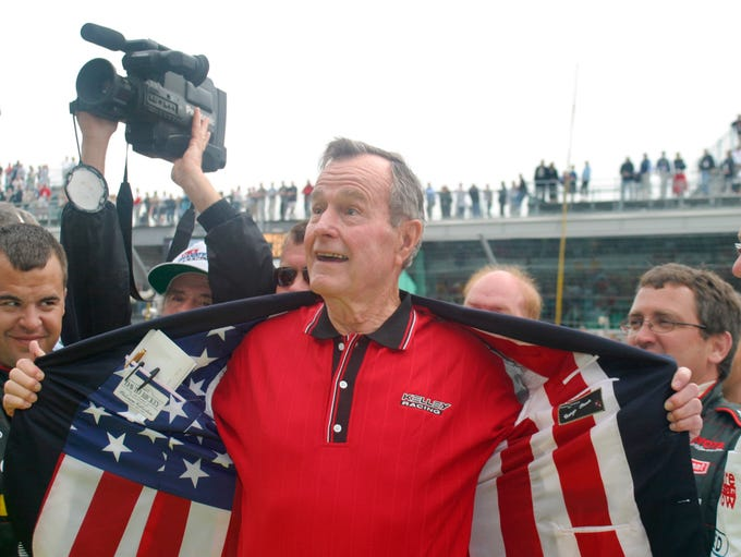 Former president George Bush shows off the flag lining