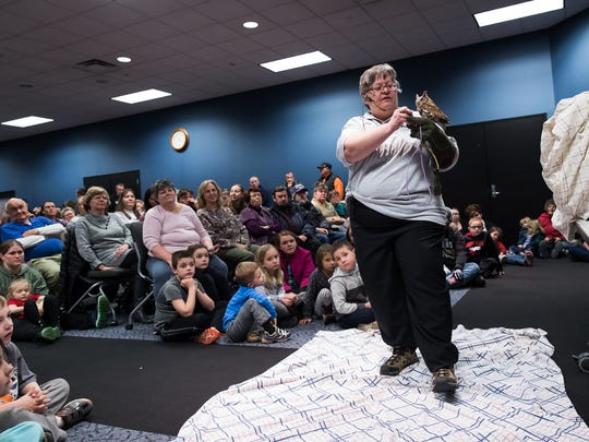 Wendy Looker, of Hanover, a licensed raptor rehabilitator, shows an eastern screech owl to a crowded room during an owl event by Rehabitat Inc. at Guthrie Memorial Library on Saturday, Jan. 28, 2017 in Hanover.  - Harrison Jones for the Evening Sun