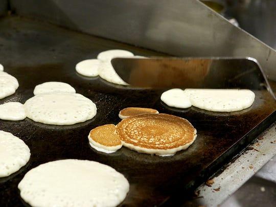 A University Kiwanian pancake cook flips over a Mickey