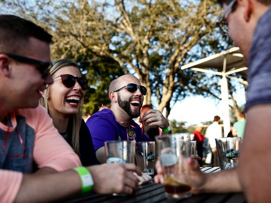 Ryan Halley, center, jokes with his friends, from left, Ryan O'Shaughnessy, Amber Nelson, Michael Piemonte, Kim Gayzur (not pictured), and Chloe Friedman (not pictured) while they sample various beers from local and national breweries at the Bonita Brew Fest at Riverside Park in Bonita Springs on Feb. 7, 2015.