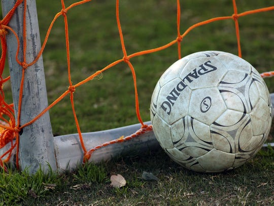 A soccer ball sits by the net during a high school