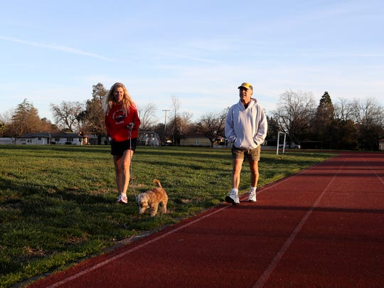 Gene Alba, right, and his wife Trish walk their dog Mutley Wednesday at Sequoia Middle School in Redding.